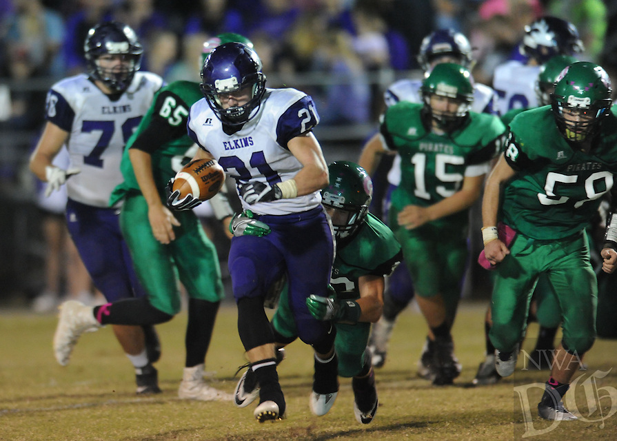 NWA Democrat-Gazette/ANDY SHUPE<br /> Colten Vaught (21) of Elkins carries the ball Friday, Oct. 28, 2016, ahead of Hunter Cartwright (center) and Trey Burnett (58) of Greenland during the first half of play at Jonathan Ramey Memorial Stadium in Greenland. Visit nwadg.com/photos to see more photographs from the game.