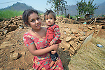 Sarita Majhi holds her one-year old daughter Sanira as she stands in front of what was once her home in Adamtar, a village in the Dhading District of Nepal. Dan Church Aid, a member of the ACT Alliance, has provided food, shelter, livelihood, winterization assistance and a variety of other support to Majhi and other indigenous villagers here in the wake of a devastating 2015 earthquake. Majhi has had to face the earthquake and its aftermath alone, as her husband is working in Saudi Arabia. He stopped sending money home and told Majhi to quit calling him.