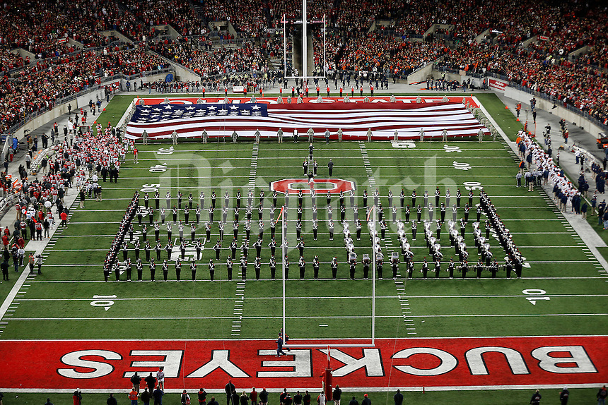 The Ohio State University Marching Band plays the national anthem as a giant American flag is flown on the field before the college football game between the Ohio State Buckeyes and the Illinois Fighting Illini at Ohio Stadium in Columbus, Saturday night, November 1, 2014. The Ohio State Buckeyes defeated the Illinois Fighting Illini 55 - 14. (The Columbus Dispatch / Eamon Queeney)