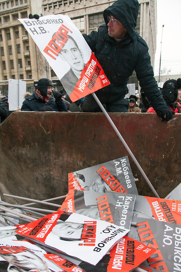 """Moscow, Russia, 13/01/2013..Protesters throw portraits of Russian politicians into a skip marked """"for garbage"""". Thousands of opposition protesters carried posters of President Vladimir Putin and members of the Russian parliament with the word ?Shame? written in red at a protest called the March Against The Scoundrels. The protest was against the new law banning the adoption of Russian children by Americans, widely seen as a response to the recently passed USA Magnitsky Act."""