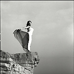 A young woman wearing a long white dress on a cliff top