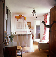 A view into a guest bedroom with a single bed draped in a sheer curtain. A stool and dressing table are placed against one wall.