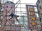 Hong Kong, 2012  A scaffold worker scrambles across the grid work of bamb oo in Hong Kong