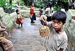 Local Lao Children selling a wish bird to free for US $1 to tourists at Pak Ou Cave in Luang Prabang, Laos.