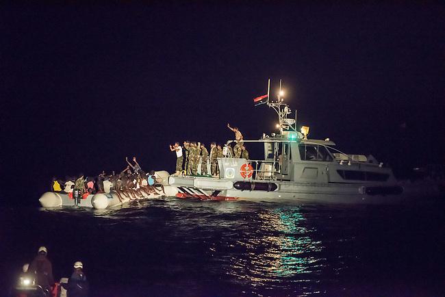 Die Sea Watch-2 Crew war am Freitag den 21. Oktober 2016 in den fruehen Morgenstunden waehrend ihrer 13. SAR-Mission vor der libyschen Kueste zu einer Position ausserhalb der 12 Meilenzone gerufen worden. Es war ein Fluechtlingsschlauchboot gesichtet worden. Als die Sea Watch-2 dort eintraf sah sie ca. 150 Menschen zusammengepfercht in einem ueberfuellten Schlauchboot sitzen. Eine Versorgung der Menschen auf dem Fluechtlingsschlauchboot mit Rettungswesten durch die Rettungs Boote der Sea Watch-2 wurde von der libyschen Kuestenwache unterbunden. Ein Soldat der Kuestenwache enterte das Schlauchboot vom Bug und machte sich dann an dem Aussenbordmotor zu schaffen. Auf dem Weg dahin schlug und trat er die Gefluechteten ein. Nach einigen Minuten entfernte sich das Boot der Kuestenwache. Dann verlor der Bug des Schlauchbootes seine Luft und es brach Panik bei den Gefluechteten aus. Sie sprangen in das Wasser und versuchten zum Schiff Sea Watch-2 zu gelangen. Die Crew warf ihnen Schwimmwesten und Rettungsringe zu, die Besatzungen der Rettungsboote der Sea Watch-2 zogen Menschen aus dem Meer, dennoch sind bis zu 30 Menschen ertrunken. Vier Ertrunkene konnten von der Sea Watch geborgen werden.<br /> Im Bild: Der Soldat der Kuestenwache macht sich am Aussenbordmotor zu schaffen.<br /> Vorne: Ein abgedraengtes Rettungsboot der Sea Watch-2.<br /> 21.10.2016, Mediterranean Sea<br /> Copyright: Christian-Ditsch.de<br /> [Inhaltsveraendernde Manipulation des Fotos nur nach ausdruecklicher Genehmigung des Fotografen. Vereinbarungen ueber Abtretung von Persoenlichkeitsrechten/Model Release der abgebildeten Person/Personen liegen nicht vor. NO MODEL RELEASE! Nur fuer Redaktionelle Zwecke. Don't publish without copyright Christian-Ditsch.de, Veroeffentlichung nur mit Fotografennennung, sowie gegen Honorar, MwSt. und Beleg. Konto: I N G - D i B a, IBAN DE58500105175400192269, BIC INGDDEFFXXX, Kontakt: post@christian-ditsch.de<br /> Bei der Bearbeitung der Dateiinformationen darf die Urh