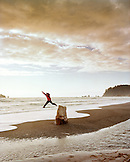 USA, Washington State, man jumping off of a tree stump at Rialto Beach, Olympic National Park