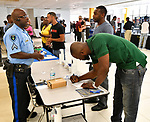 Maplewood Police Cpl. Steve Jamerson (left) speaks with Quintin White (standing at right) as Jamil Foster fills out an application form at a Diversity Fair sponsored by the St. Louis County branch of the Ethical Society of Police. The fair was held at Hazelwood Central High School on Saturday August 11, 2018 with police agencies from ten different jurisdictions represented.   Photo by Tim Vizer