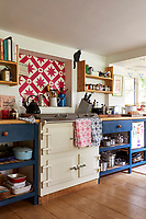 Bold colours and patterns feature in the kitchen. A cream Aga sits between the blue painted shelving units.