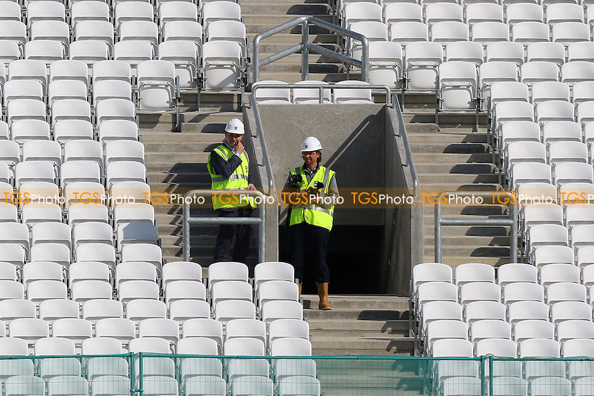 Construction workers look on as a news stand is built during Surrey CCC vs Middlesex CCC, Friendly Match Cricket at the Kia Oval on 22nd March 2016