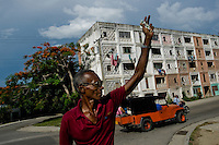 A Cuban man waves to his friend in Abel Santamaría, the social housing neighbourhood of Santiago de Cuba, Cuba, 31 July 2008. About 50 years after the national rebellion, led by Fidel Castro, and adopting the communist ideology shortly after the victory, the Caribbean island of Cuba is the only country in Americas having the communist political system. Although the Cuban state-controlled economy has never been developed enough to allow Cubans living in social conditions similar to the US or to Europe, mostly middle-age and older Cubans still support the Castro Brothers' regime and the idea of the Cuban Revolution. Since the 1990s Cuba struggles with chronic economic crisis and mainly young Cubans call for the economic changes.