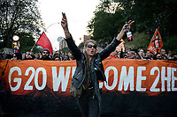 "GERMANY, Hamburg, protest rally ""G-20 WELCOME TO HELL"" against G-20 summit in july 2017, black block with mummed people, woman in leather clothes with beer bottle /DEUTSCHLAND, Hamburg, Landungsbruecken, Protest Demo WELCOME TO HELL gegen G20 Gipfel , vermummte Demonstranten des schwarzen Block,  Punk Frau mit Leder Kleidung und Bierflasche"