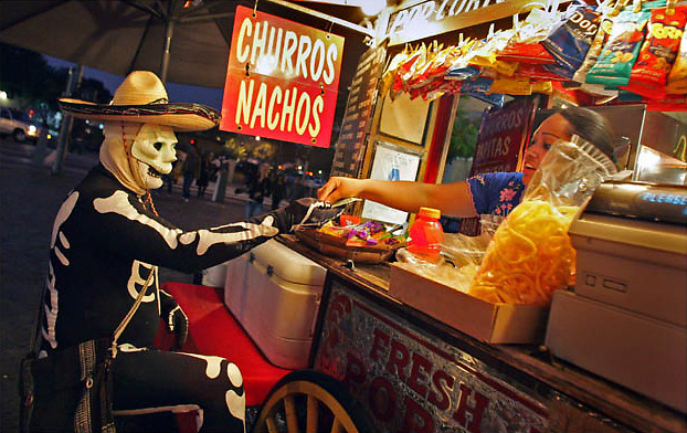 Fernando Muro of Anaheim stops for a churro before the Dia De Los Muertos (Day of the Dead) celebration is observed at the at Plaza De La Raza next to Olvera Street in Los Angeles Thursday November 01, 2007.