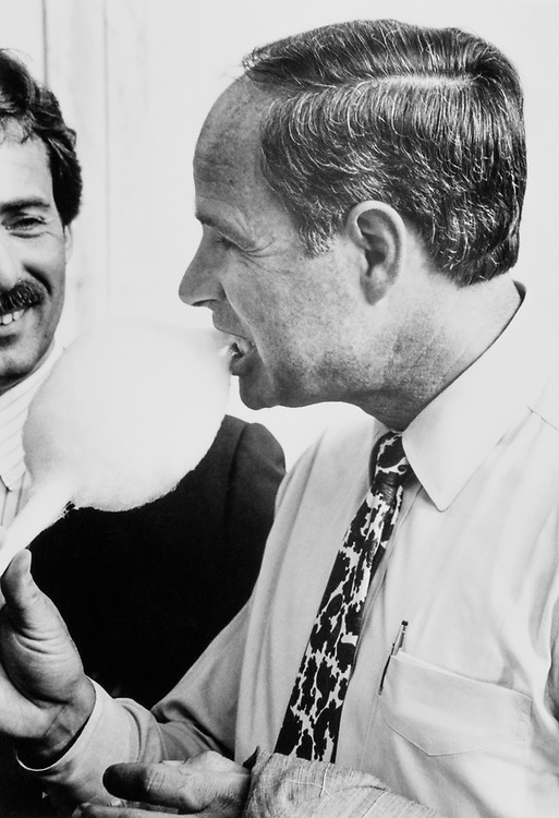 Rep. James W. Grant, R-Fla. eating cotton candy while Rick Walsh, employee of General Mills, looks on. General Mills was one of the  sponsors of the Florida State Delegation Party on July 11, 1989. (Photo by Maureen Keating/CQ Roll Call)