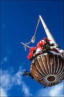 An airplane above a basket of red Christmas flowers on a lamppost. New Jersey.