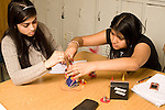 Education High School science class physics lab two female students working together on electricity lab