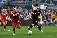 USWNT midfielder Heather O'Reilly (9) goes for the ball against Canada's Christina Julien.....USWNT played to a 1-1 tie with Canada at LIVESTRONG Sporting Park, Kansas City, Kansas.