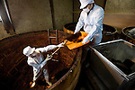 Nobutaro Asai, president of Maruya Hatcho Miso Co., stands by giant vats of fermenting miso at his company' factory in Okazaki City, Aichi Prefecture Japan on 11 Dec. 2012. Photographer: Robert Gilhooly
