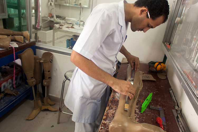 A man makes an artificial leg for victims of land mines at a hospital in Phnom Penh, Cambodia administered by the NGO Cambodia Trust. <br /> <br /> Photos &copy; Dennis Drenner 2013.