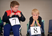 STAFF PHOTO BEN GOFF  @NWABenGoff -- 12/10/14 Donovan Miles, left, and Cole Wilson, both 9, react after a competitor gave an incorrect answer and was eliminated during a vocabulary round in the school spelling bee at Bonnie Grimes Elementary in Rogers on Wednesday Dec. 10, 2014. Two top spellers from each 4th-6th grade classroom competed in the bee, with winner Denis Carranza advancing to the county bee.