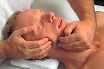 hands massaging patient's jaw