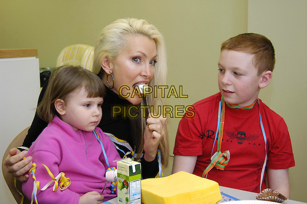 CAPRICE BOURRET.Hosts childrens Tea Party in the new Patient Hotel (sponsored by Bid TV) at Great Ormond Street Hospital, London, February 22nd 2004..portrait headshot Bouret funny face kids eating mouth.Ref: HT.www.capitalpictures.com.sales@capitalpictures.com.©Capital Pictures.