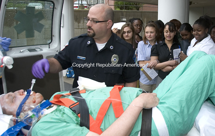 WATERBURY, CT. 09 May 2008-050908SV17--Wilby High School students watch Paramedic Kris Fazzone work on Dr. Jeffery Sedlack, Associate Director of the Department of Trauma Services, as he plays a stabbing victim during a drill at Waterbury Hospital in Waterbury Friday.<br /> Steven Valenti Republican-American