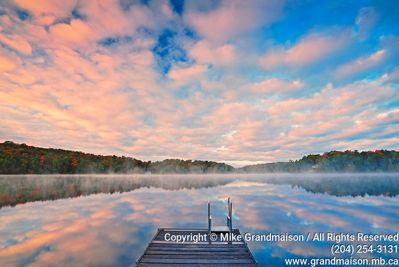 Dock and clouds reflection in Horseshoe Lake at sunrise<br />Horseshoe Lake<br />Ontario<br />Canada