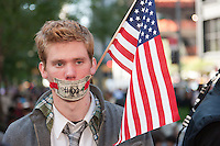 A protester stands with his mouth covered by a dollar bill flanked by an American flag in Zuccotti Park during the Occupy Wall Street demonstration in New York City, New York.