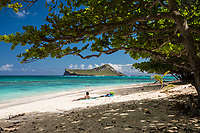 A sunbather looks out at other beachgoers and at Rabbit (or Manana) Island, Waimanalo Beach, Windward O'ahu.