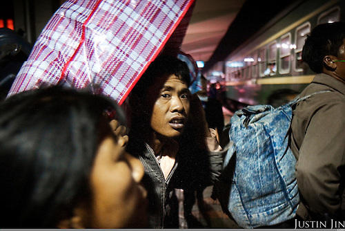 "Workers carrying their possessions rush for the train in Guangzhou city, China, as their head home to celebrate new year. .This picture is part of a photo and text story on blue jeans production in China by Justin Jin. .China, the ""factory of the world"", is now also the major producer for blue jeans. To meet production demand, thousands of workers sweat through the night scrubbing, spraying and tearing trousers to create their rugged look. .At dawn, workers bundle the garment off to another factory for packaging and shipping around the world..The workers are among the 200 million migrant labourers criss-crossing China.looking for a better life, at the same time building their country into a.mighty industrial power."