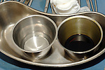 Two stainless steel wash bins and a stainless steel kidney dish. The shape of the dish enables it to be easily held against the body. Royalty Free