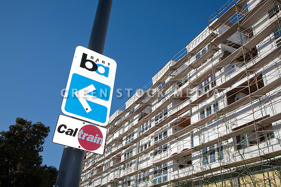 A low angle view of BART and Caltrain road signs by a scaffolded condo. The Millbrae Paradise mixed use construction project located on El Camino Real in Millbrae, CA is a great example of transportation oriented development (TOD) since it is located a very short walking distance from the Millbrae Transit Hub featuring Caltrain, BART, and bus mass transportation options ideal for both commuter and recreational uses. The project features 142 residential condominiums and 10 commercial condo spaces for restaurants or retail stores. Millbrae, California, USA