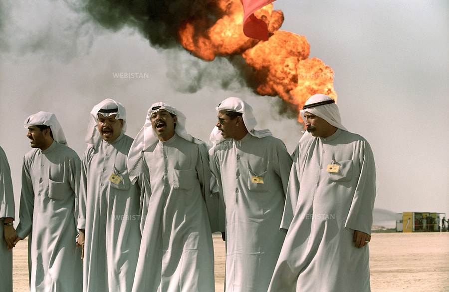 Traditional dancers and musicians perform at the celebration of extinguishing the last oil well set ablaze by the Iraqi forces, in Al Ahmadi, nine months after the withdrawal of Iraqi troops from Kuwait. In the background an oil well can be seen still burning...During withdrawal, the Iraqi army practiced a scorched earth policy by placing land mines and setting fire to Ku-waiti oil wells. More than 500 oil wells were burning in Kuwait. The inferno took over nine months to extinguish; the costs to restore the Kuwaiti petrol infrastructure exceeded 5 billion US dollar. ..The celebration was attended by the Emir and other members of the Al-Sabah royal family.