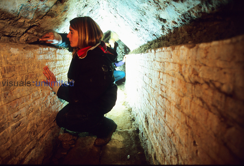 Archaeologist studying an underground duct beneath the big thermae that still functions to carry waters coming from the pool of the Canopus, Villa Hadriana, Italy.