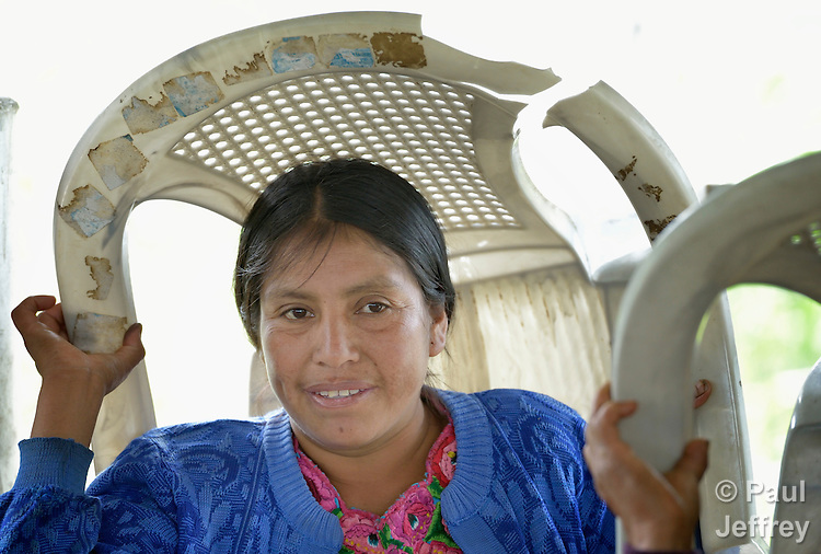 A woman holds a chair over her head as she participates in a workshop at an eco-agricultural training center in Comitancillo, Guatemala. The center is sponsored by the Maya Mam Association for Investigation and Development (AMMID).