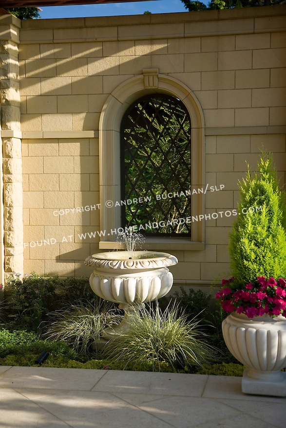 a small water fountain and a colorful container planting decorate an outside private nook in the late afternoon sunlight at the side of a grand estate