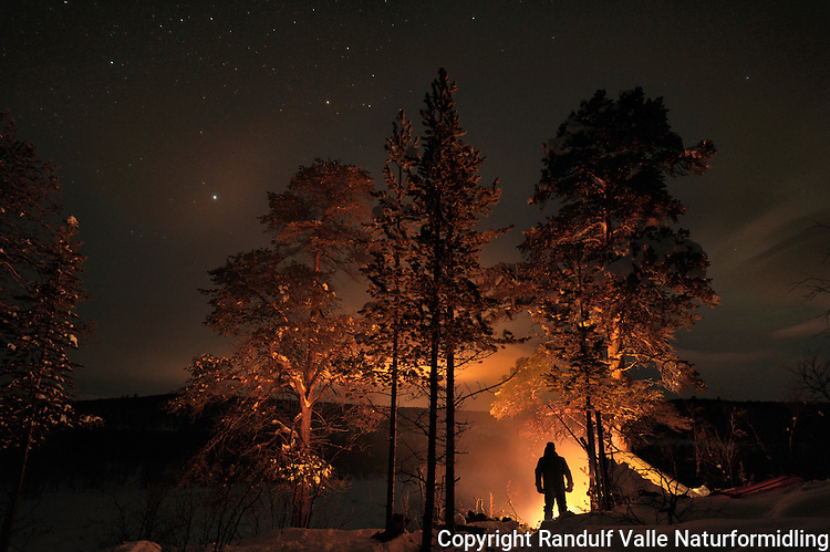Mann foran tyribål. ---- Man in front of camp fire.