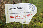 Damaged fishing association sign at Ladies Bridge, Pewsey Vale, Wiltshire, England, UK
