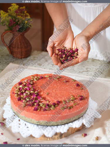 Closeup of woman hands decorating a home-made strawberry cake with rose buds and pumpkin seeds at home