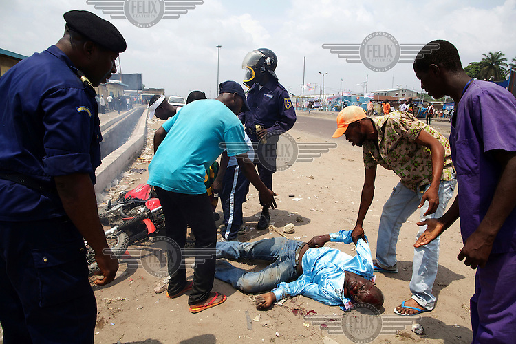 People attend to a motorcyclist who was attacked and stoned during violence leading up to the DRC's presidential and National Assembly elections.