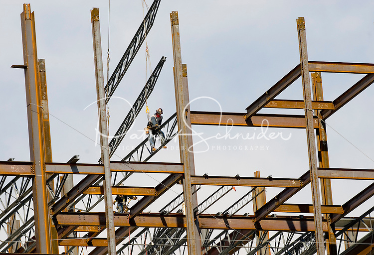 A construction worker balances atop the steel frame of a new high rise growing in downtown Charlotte, NC