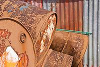 Rusting marine fuel oil drums behind building, Steine, Lofoten islands, Norway