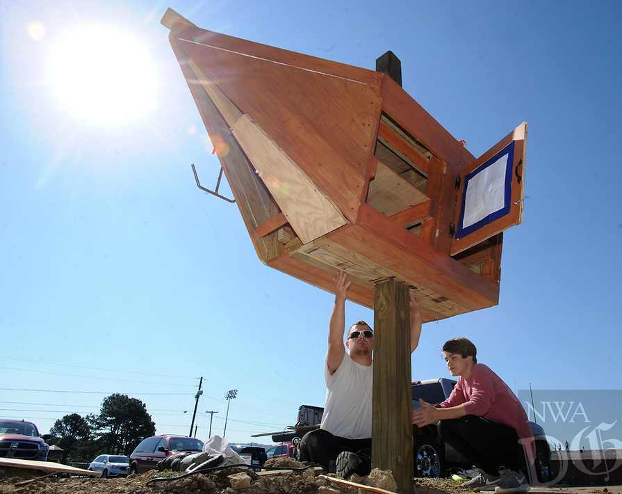 NWA Democrat-Gazette/ANDY SHUPE<br /> David Sanford (right), 13, an eighth-grader at Greenland Middle School, works with friend Dylan Wright Tuesday, May 16, 2017, to install a Little Free Library built by Sanford to resemble a Pirate ship outside the school. The mascot of the school district is a Pirate. Sanford built the library as a year-long project for his Environmental and Spatial Technologies class at the school. The structure will house and protect books that are free to others on a take-one, leave-one basis.