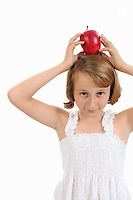 Girl (10) balancing red apple on head (Licence this image exclusively with Getty: http://www.gettyimages.com/detail/103301311 )