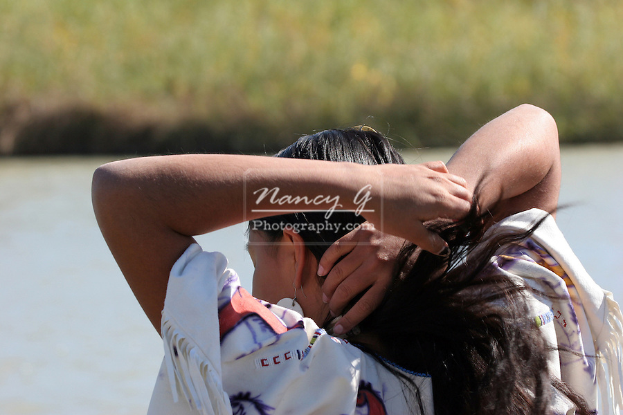 A young Native American girl walking along the rivers edge in South Dakota fixing her hair