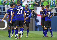 Manchester United defender Patrice Evra, second from right and forward Michael Owen celebrate a goal during play against the Seattle Sounders FC at CenturyLink Field in Seattle Wednesday July 20, 2011. Manchester United won the match 7-0.