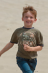 Running and smiling boy outdoors on the sand dunes