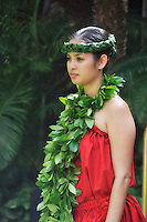 A hula dancer with an open-ended maile lei and a woven ti leaf headband before a performance at the Hilton Hawaiian Village resort in Waikiki, O'ahu.