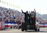 Nov 10, 2013; Pomona, CA, USA; NHRA funny car driver John Force , top fuel dragster driver Shawn Langdon and pro stock motorcycle rider Matt Smith celebrate with championship trophy during the Auto Club Finals at Auto Club Raceway at Pomona. Mandatory Credit: Mark J. Rebilas-