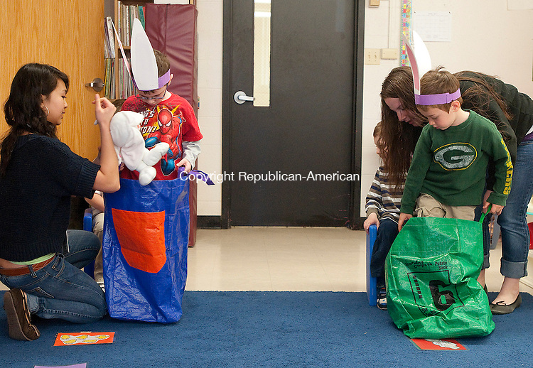 TORRINGTON, CT, 14 APRIL 2011-041411JS13-- Torrington High School sophomore Thienthanh Trinh gets  with Matthew McCarthy ready for a sack race, left, as Junior Lyndsey Richards, right helps Jackson Valunas get ready Thursday at the preschool laboratory at Torrington high School. The lab is about to mark its 30th anniversary. <br /> Jim Shannon/Republican-American